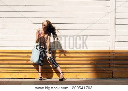 Outdoor portrait of a young beautiful fashionable happy lady wearing sunglasses, in a wooden frame, against a wooden, white wall. The model wears stylish clothes, a beige blouse, black breeches in a white stripe, a bag of light blue.