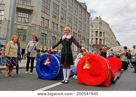 Moscow Russia - September 10 2016: Girl in soviet school uniform and with string bags waiting for players