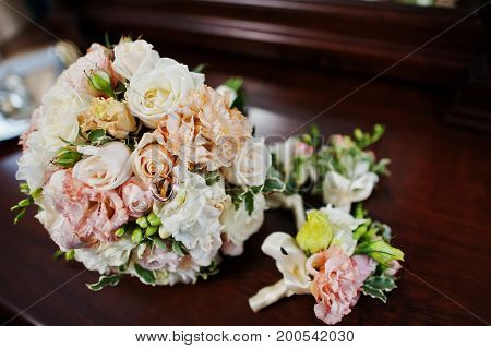 Close-up Photo Of A Wedding Bouquet And Buttonhole Flowers Laying On The Table.