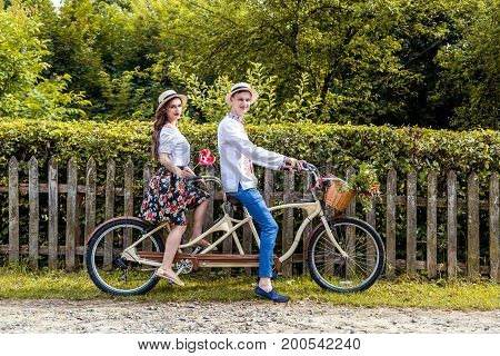 Young couple riding a bike tandem in the park.