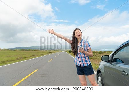 Pretty Woman With Hand Up Calling Passing Car