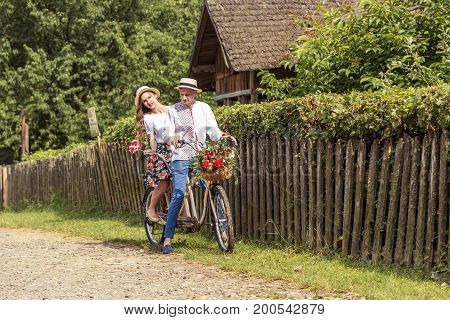 Young couple with bike tandem in park. The girl holds a candy in the form of a heart.