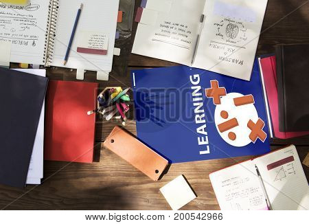 Aerial view of mathematics solution lessons on wooden table