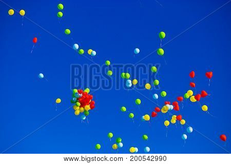Group of multicolored helium filled balloons in the blue sky