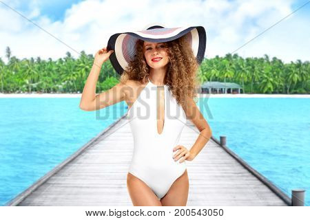 Beautiful woman posing on a wooden pontoon at tropical resort