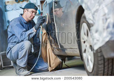 auto repairman grinding autobody bonnet