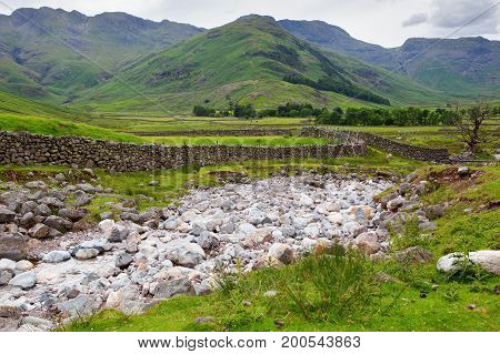 Beautiful views in Lake District National Park, England, stone walls, stream, mountains on the background, selective focus