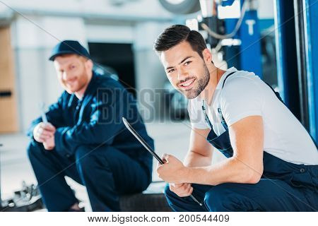 Automechanics Sitting On Floor