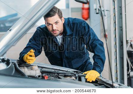 Automechanic Looking Under Car Hood