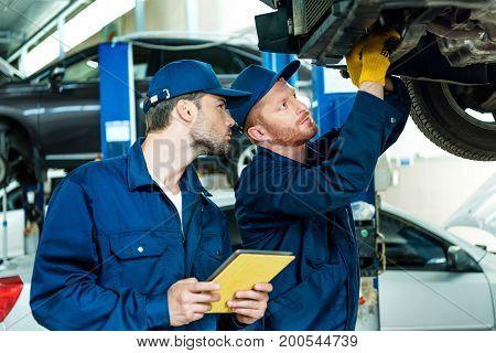 Automechanics Working On Car