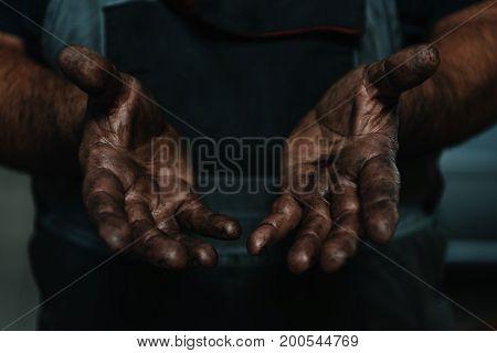 Closeup of male hands covered in machine oil.