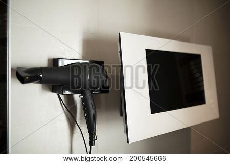 Picture of black hairdryer and white monitor in bathroom