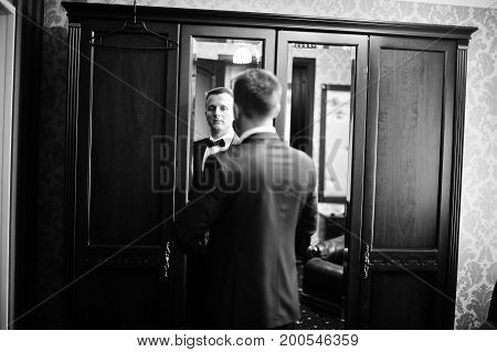 Portrait Of A Stunning Groom Dressing Up For The Wedding And Getting Ready In His Room. Black And Wh