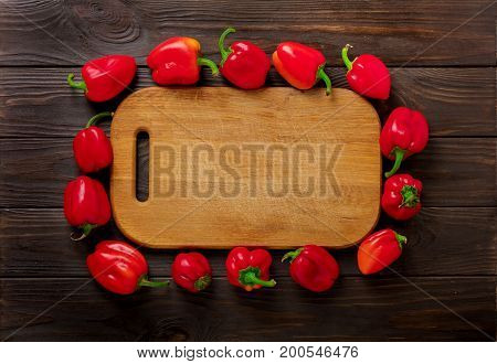 Sweet bulgarian red peppers and cutting board on a dark wooden background. Selective focus.