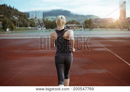 A Woman Runs Through The Stadium. A Healthy Way Of Life.