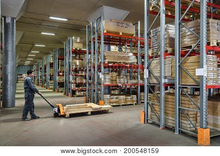 Moscow - August 1, 2017: The worker with fork pallet truck stacker works in the warehouse. Moscow is a modern city with well-developed logistics infrastructure.