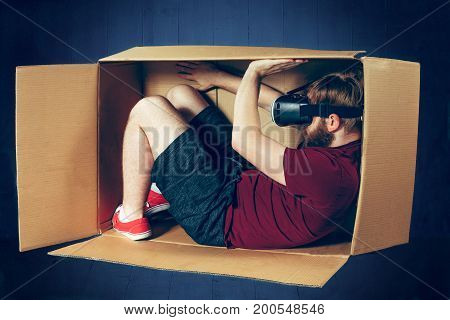 Introvert concept. The man sitting inside box with glasses of virtual reality. Future technology concept.