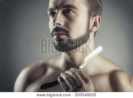Closeup of young handsome man guy with beard showing razor blade studio shot. Shave concept