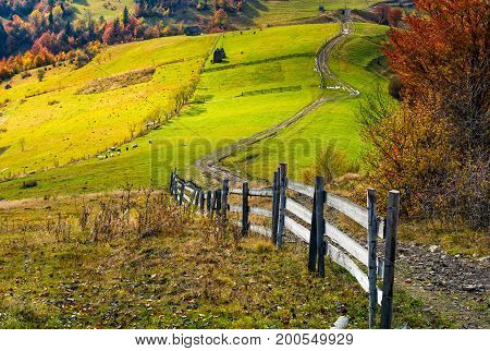 beautiful deep autumn countryside scene. wooden fence near the path through rural fields on hills in Carpathian mountainous area