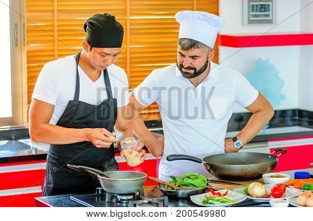 Colleagues At Work: Thai And European Chefs At The Kitchen Doing Thai Food