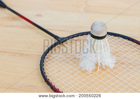 close-up old shuttlecock on badminton racket on wooden background