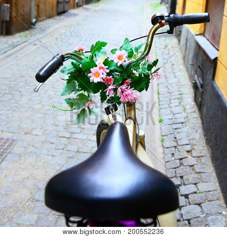 Bicycle with bunch of flowers on handle bar in Stockholm, Sweden. Shallow DOF!