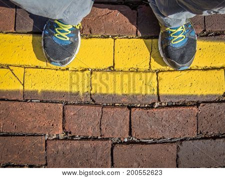 Waiting behind a yellow line - man's feet on a train station platform