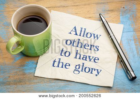 Allow others to have a glory - handwriting on a napkin with a cup of espresso coffee