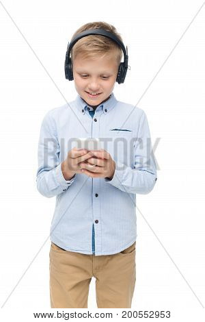 portrait of smiling preteen boy in headphones using smartphone isolated on white