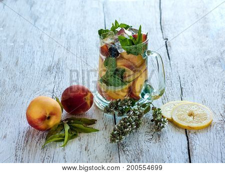 Soft dreank with peaches ice and lemon in glas cup on wooden table