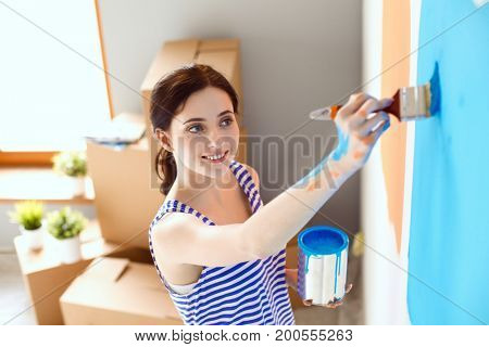 Happy smiling woman painting interior wall of new house. Happy smiling woman