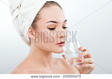 Girl With Naked Shoulders And White Towel Drinking Water