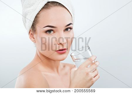 Girl With Naked Shoulders And White Towel Holding Glass Of Water