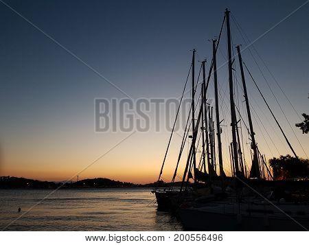 silhouettes of sail poles at sun set