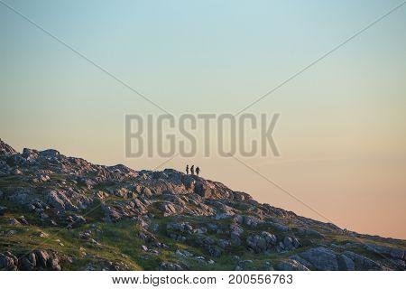 four friends on rocky hillside at sunset; Fogo Island, Newfoundland