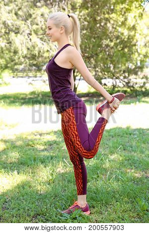 Young beautiful woman doing sport exercises for legs in park