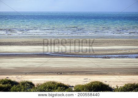Low tide and motion flying sand at the North sea in Belgium De Panne