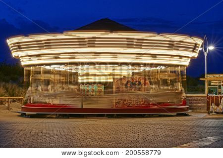 Merry-go-round on the Promenade of the Belgian Seaside resort De Panne in motion and illuminated by night