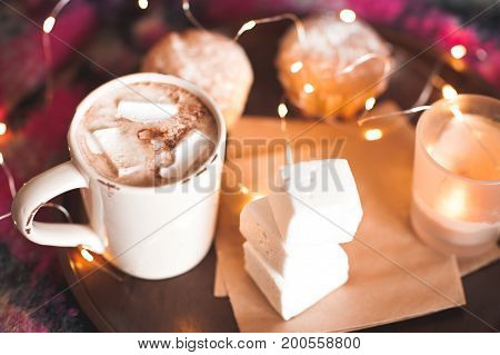 Mug with coffee and marshmallow with cake and candle stay on wooden tray over christmas lights background. Good morning. Selective focus.