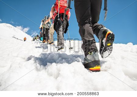 A close-up of the legs of a group climbing uphill climbing the top of Elbrus