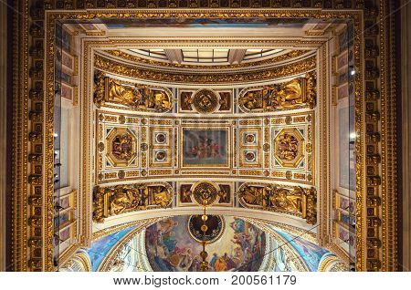 ST PETERSBURG RUSSIA - AUGUST 15 2017. Ceiling ornated with sculptures and Bible paintings in the interior of the St Isaac Cathedral in St Petersburg Russia. Interior view of St Petersburg landmark