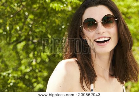 Beautiful carefree brunette woman laughing in sunglasses