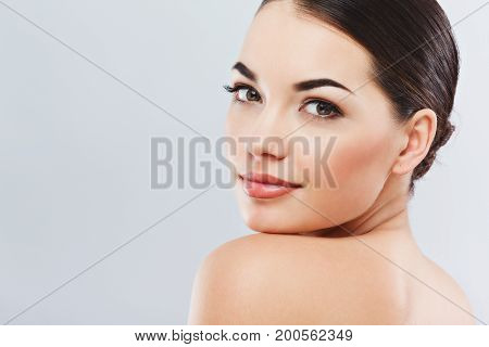 Cute Girl With Dark Hair At Gray Studio Background