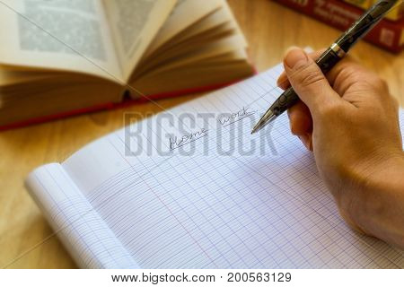 hand with pensil writes something in the copybook