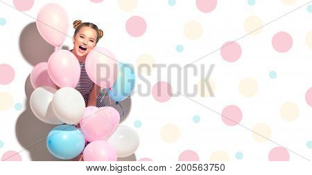 Beauty girl with colorful air balloons laughing isolated on white background. Beautiful Happy Young woman on birthday holiday party. Joyful model having fun and celebrating. Polka dots background