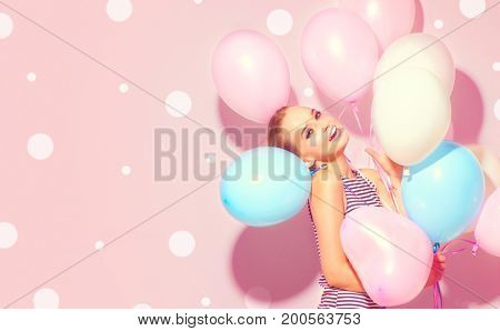 Beauty girl with colorful air balloons laughing over pink background. Beautiful Happy Young woman on birthday holiday party. Joyful model having fun, playing and celebrating. Polka dots background