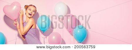 Beauty girl with colorful air balloons laughing over pink background. Beautiful Happy woman on birthday party. Joyful model having fun, playing and celebrating with pastel color balloons. Wide screen