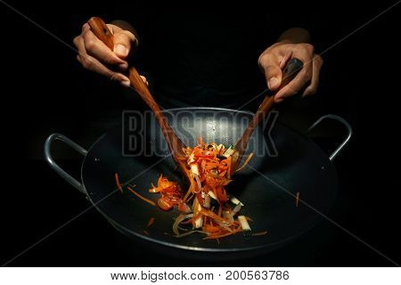 Hands of working chef preparing a noodle with tomato zucini and carrot in wok in darkness. Traditional way of cooking pad thai on wok frying pan.
