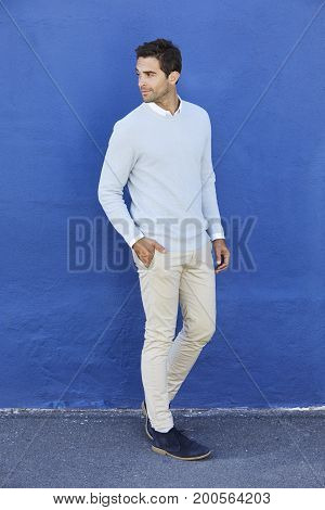 Man in blue sweater and chinos looking away