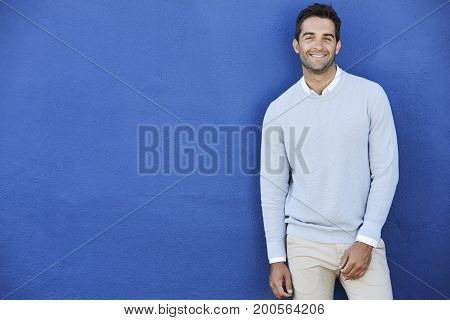 Smiling man in blue sweater against blue wall portrait